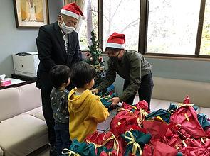 子どもたちにクリスマスプレゼントを渡す様子