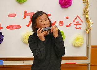 ハーモニカの演奏を披露してくださる田中さんの写真