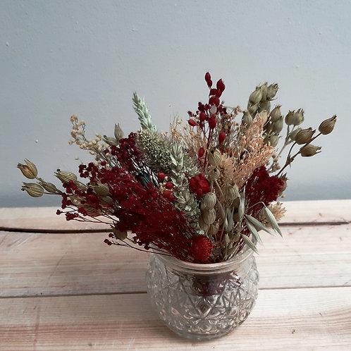 Bouquet dans les tons vert et rouge et pot en verre