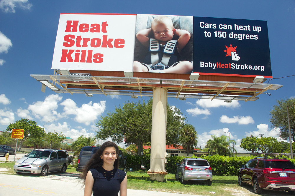 Kelly Ann, Founder of Baby Heat Stroke, standing in front of a donated billboard supporting child safety