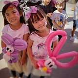 Twin Girls with Faces Painted holding ba