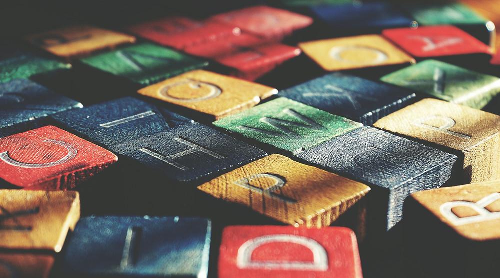 színes fakockák közelről, mindegyiken egy-egy betű