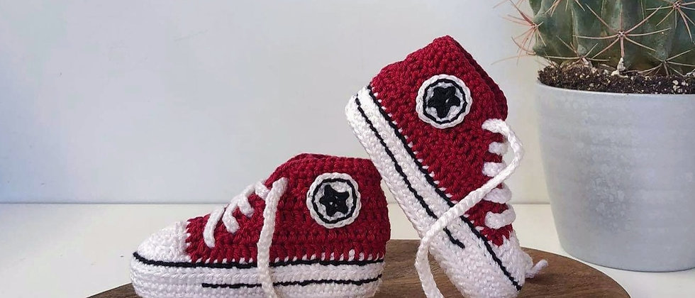 red baby booties posed