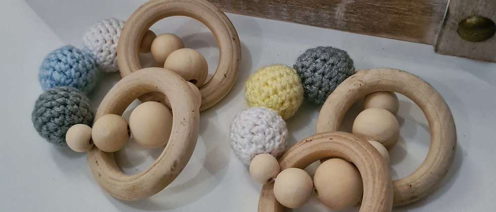 grey with blue and yellow wooden rattles for babies close up