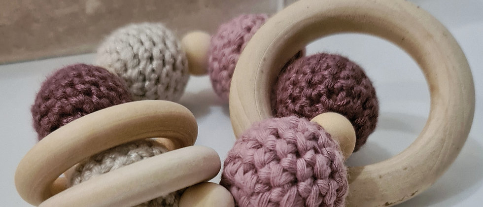 pink wooden rattle for babies side view close up