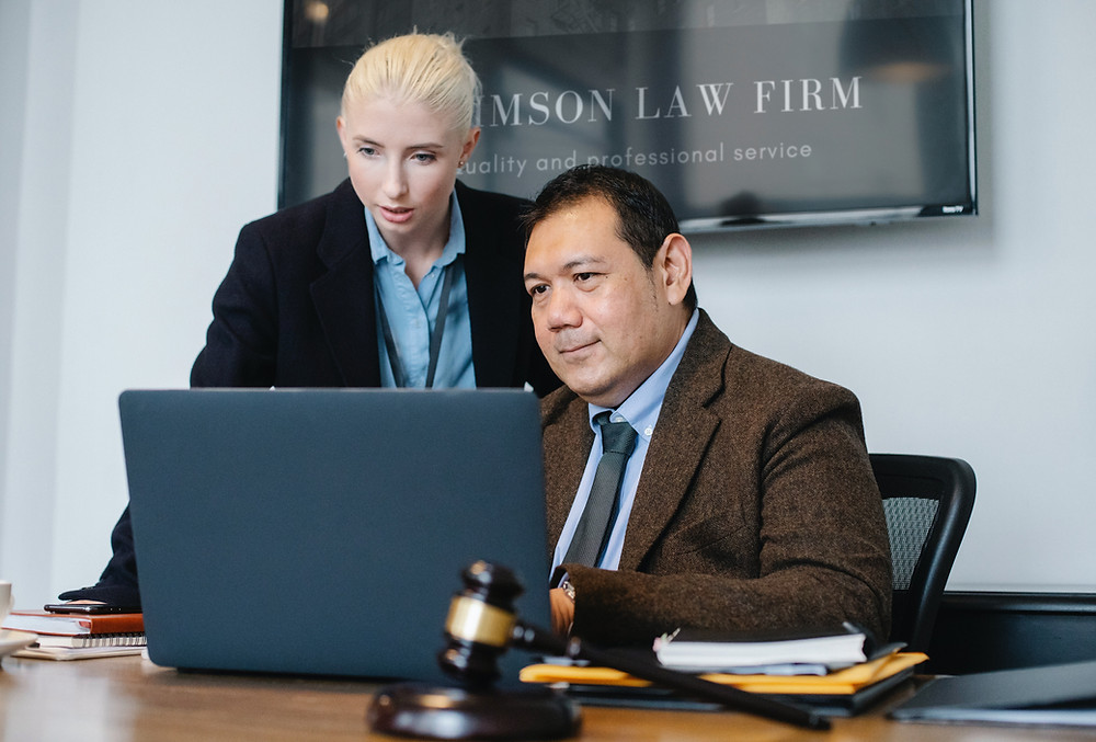 Two lawyers looking at a laptop screen inside a law office