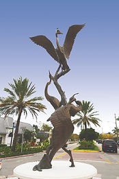 The Three Heron Fountain, a bronze sculpture created by Artist Geoffrey C. Smith, shows the interaction between 3 herons and is located in Stuart, Florida.