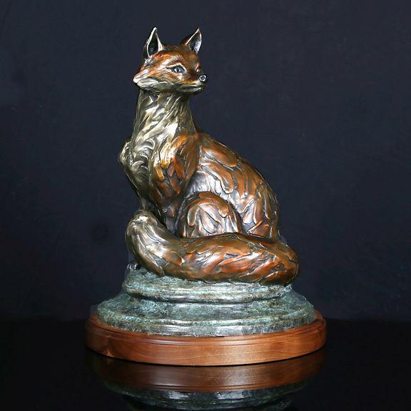 A bronze sculpture of a red fox sitting.