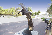 Skimming the Waves, a Life Size Pelican bronze sculpture created by Artist Geoffrey C. Smith, shows a pelican in flight and is located in Stuart, Florida.