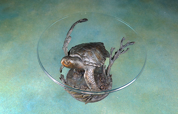 A bronze sculpture table of a sea turtle swimming in a reef.
