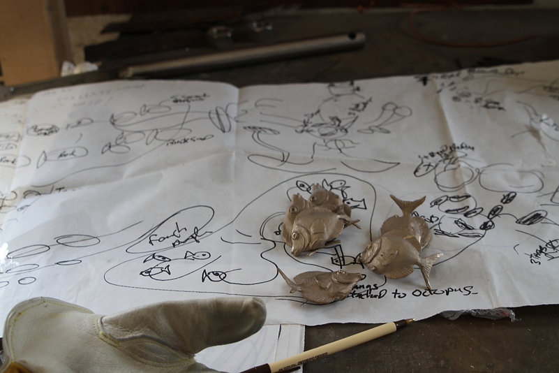 Small bronze fish laying on a sketch of plans for a reef sculpture at the foundry.