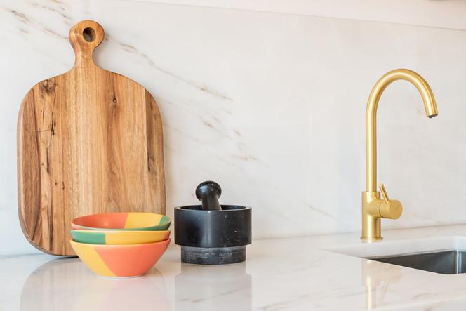 Detalhes de bancada de cozinha com torneira dourada