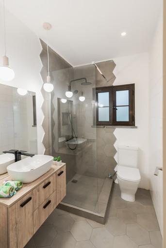 Reabilitação total de casa-de-banho com torneiras preto mate e mosaico tipo microcimento