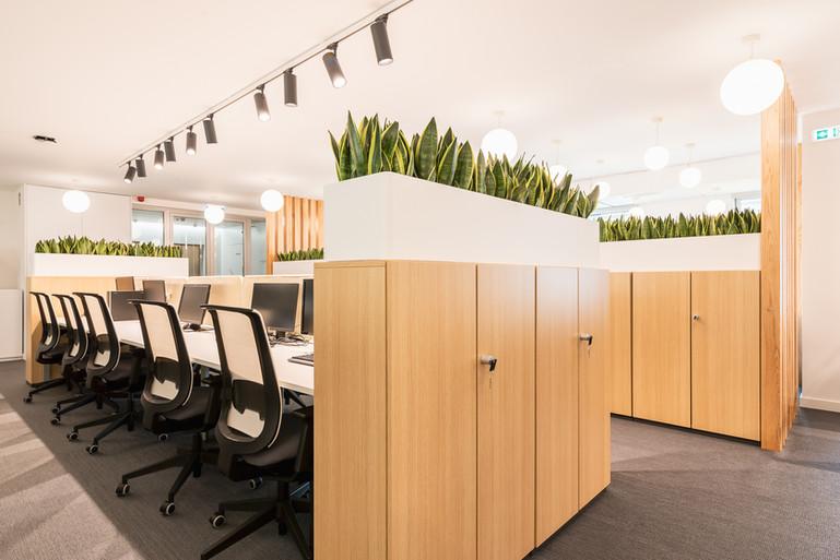 Ilhas de trabalho com arrumação e floreiras nos topos para privacidade