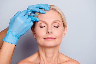 Portrait of calm serious aged woman with wrinkle keeping eyes close getting injection in f