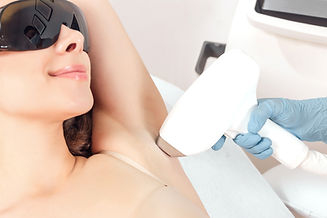 Young woman making body hair removal laser depilation in beauty center.jpg
