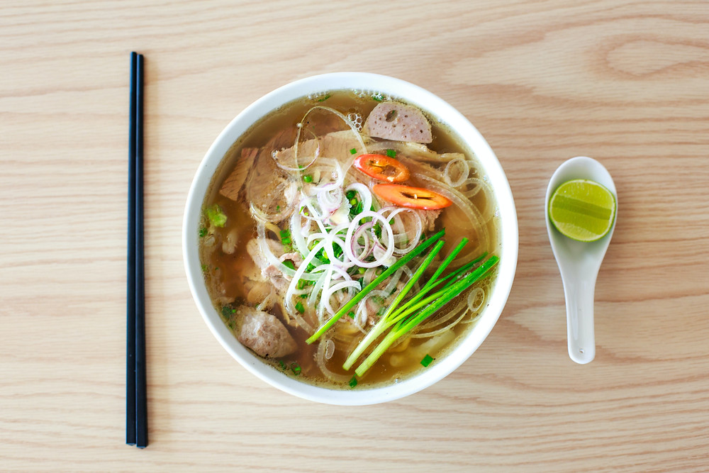A bowl of pho with meatballs, noodles, and topped with veggies. A set of black chopsticks are on the left. A ceramic spoon with half a lime in it is on the right.