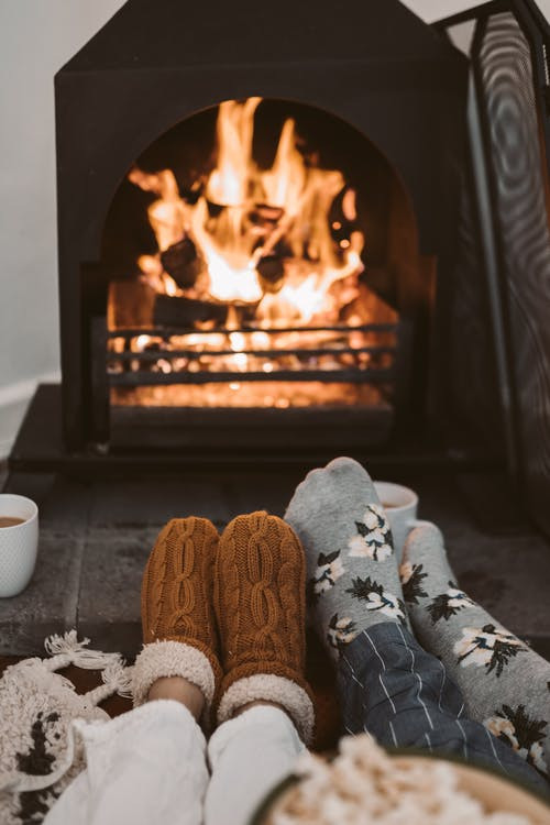 An image of two people's feet with socks on and warming them in front of a cozy fireplace.