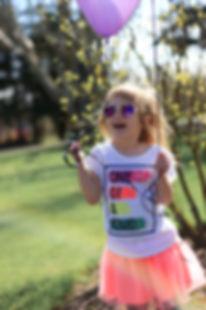 A happy girl holding purple balloon.