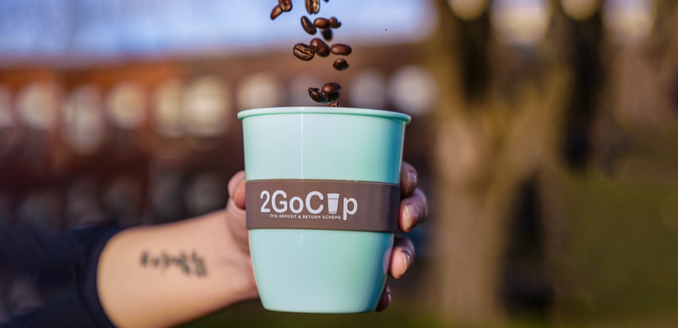 Woman holding 2GoCup coffee cup with coffee beans being poured into it