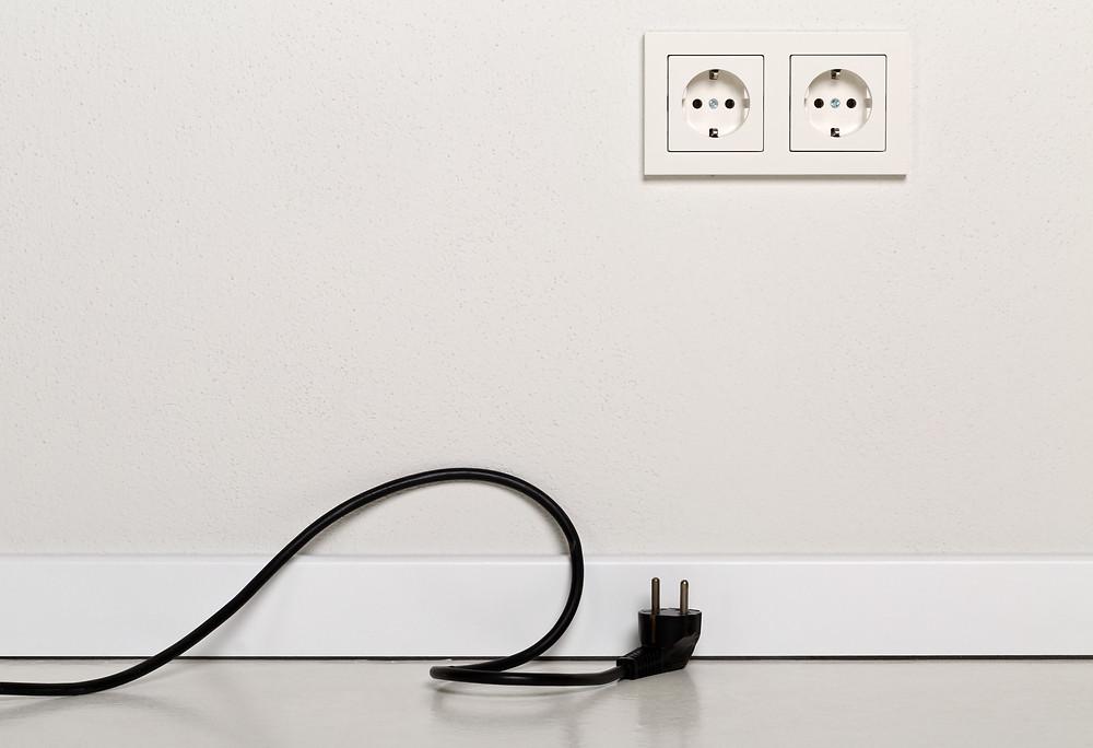 black chord plug on the floor, unplugged