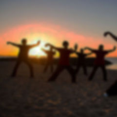 A group of gout patients performing Tai Chi on the beach at sunset.