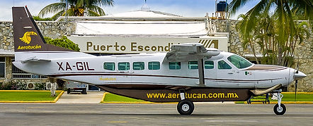 An Aerotucan Cessna Caravan parked in front of the Puerto Escondido airport building.