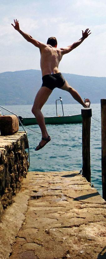Man having an active life and jumping into a lake.
