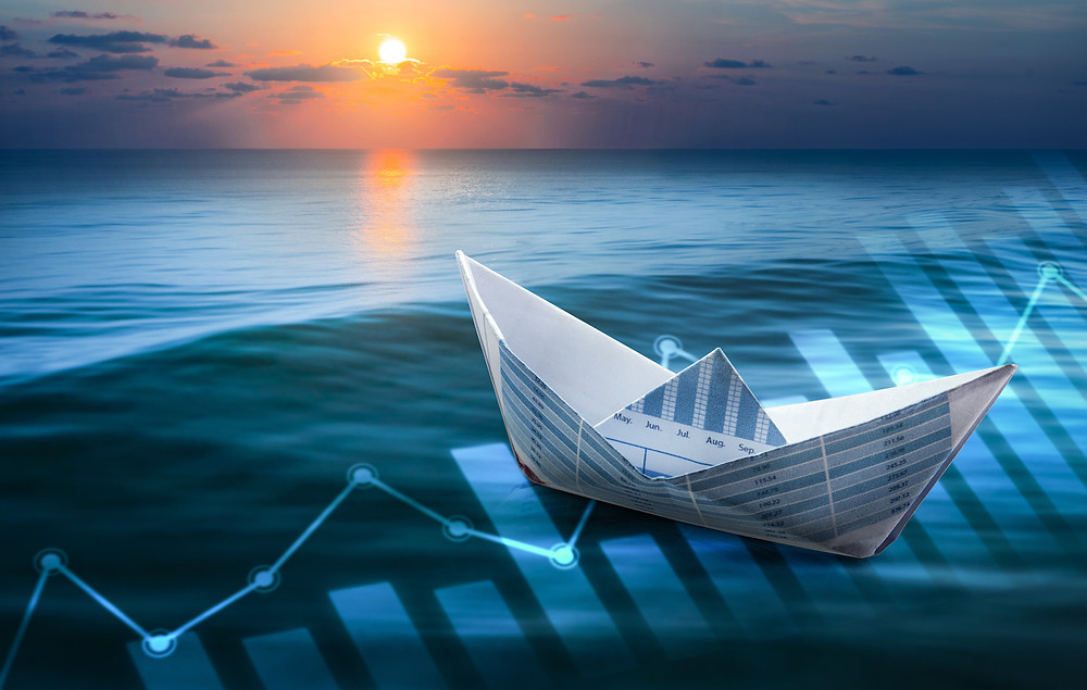 """Der Beitrag heißt: """"Langsam denken, erfolgreich handeln"""". Das Bild zeigt ein Papierboot aus einem Kalenderbogen, das auf dem Meer schwimmt, die Sonne steht tief am Horizont, im Meer spiegeln sich Diagramme."""