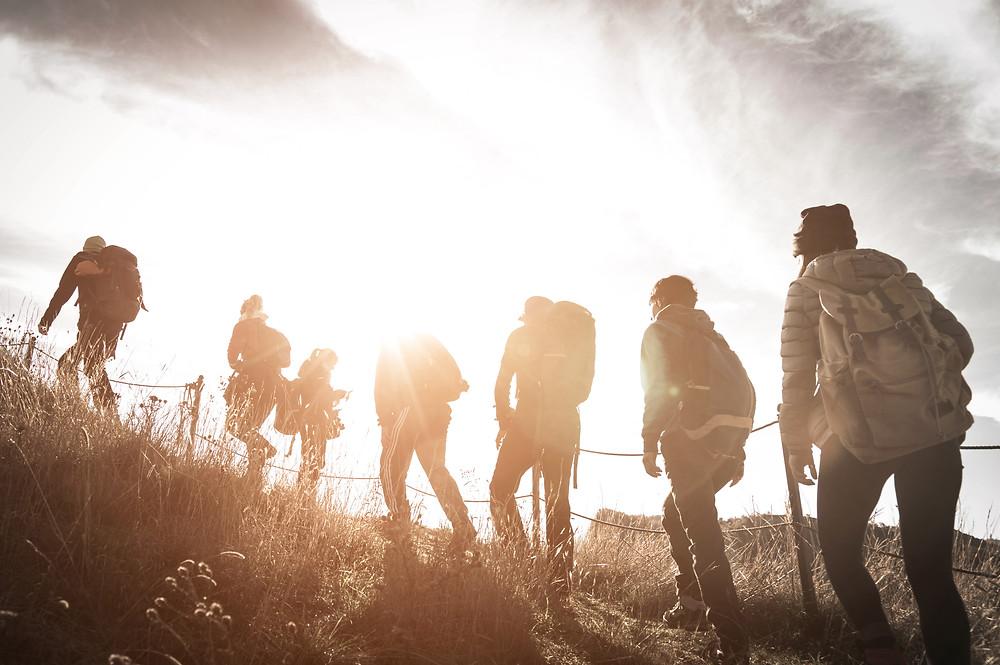 Der Artikel heißt: Backpacking statt all-inclusive – die Reise auf die New-Work-Insel. Das Bild zeigt siebenjunge Personen, die im Sonnenuntergang auf einem Berg Backpacken.