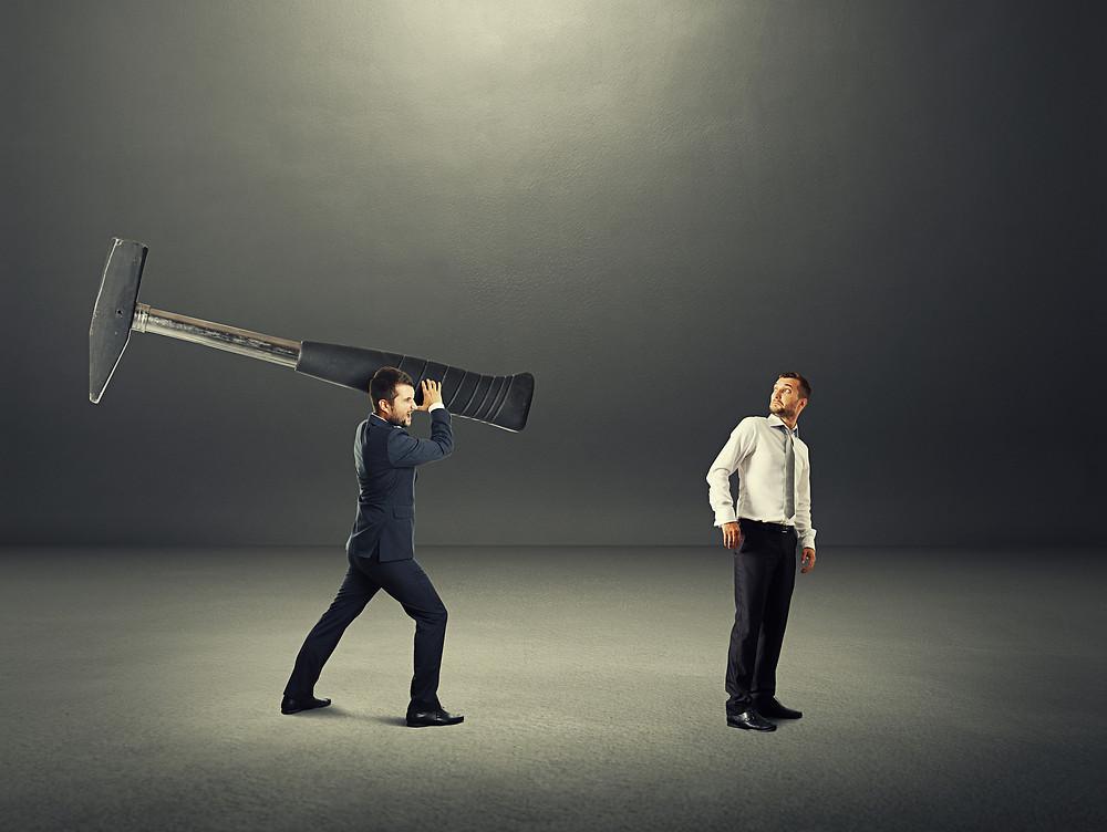 """Der Beitrag heißt: """"Stopbossing – Verändern Sie Ihr Unternehmen"""". Das Bild zeigt einen Mann im dunklen Anzug, der hinter einem Mann ohne Sakko mit einem überdimensional großen Hammer ausholt."""