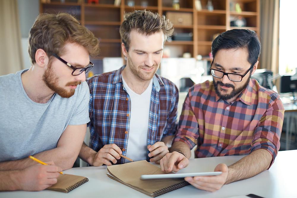 Der Artikel heißt: Unternehmerisches Denken kommt von ungefähr. Das Bild zeigt drei Mitarbeiter im kreativen Gespräch.