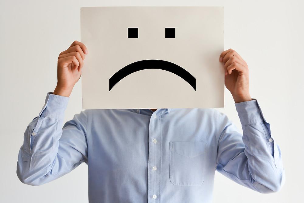 Der Artikel heißt: Der Teufelskreis des kleinen Wehwehchens. Das Bild zeigt  einen Mann, der vor sein Gesicht ein Blatt mit aufgemalten Traurig-Smiley hält