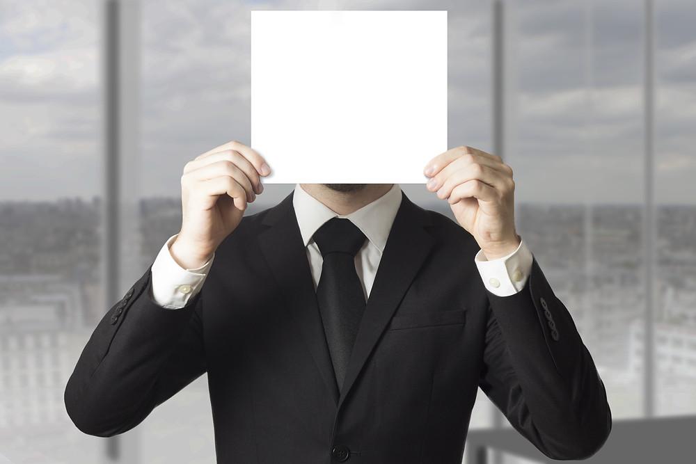 """Der Artikel heißt """"Nicht-Auffallen ist die neue Aufmerksamkeit"""". Das Bild zeigt einen Unternehmer in Anzug und Krawatte, der sich ein leeres weißes Blatt Papier vor das Gesicht hält."""