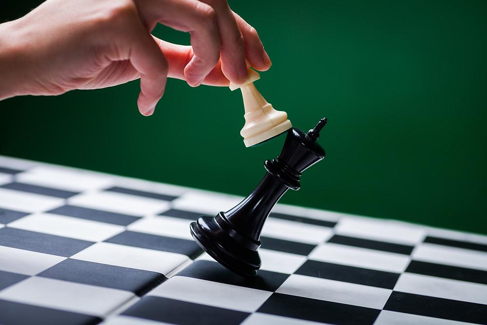 """Der Beitrag heißt: """"Wissen ist Macht – und muss deshalb geteilt werden!"""" Das Bild zeigt eine Hand, die mit einer weißen Schachfigur eine schwarze Schachfigur umwirft."""