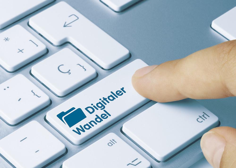 """Der Artikel heißt: Die Digitalisierung muss menschlicher werden. Das Bild zeigt eine PC Tastatur mit Taste """"Digitaler Wandel"""", die ein Zeigefinger drückt."""