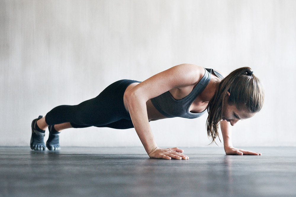 a woman performs a strong and powerful pushup