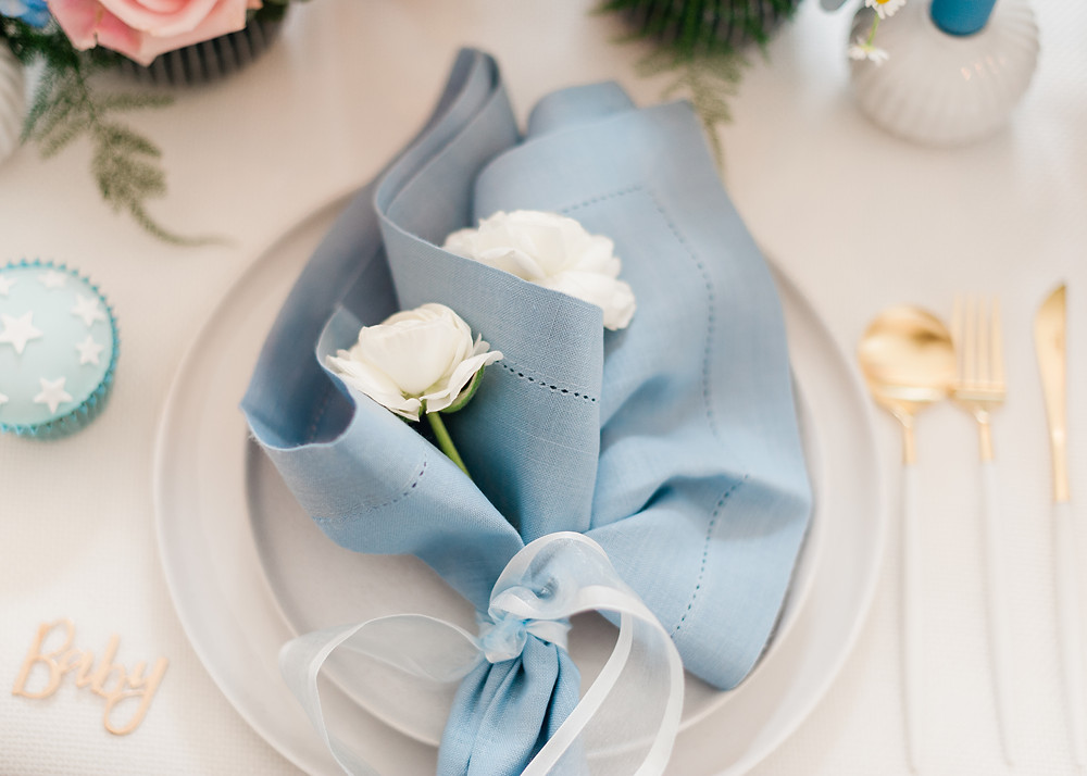 Blue place setting decor with ribbon and white and gold cutlery