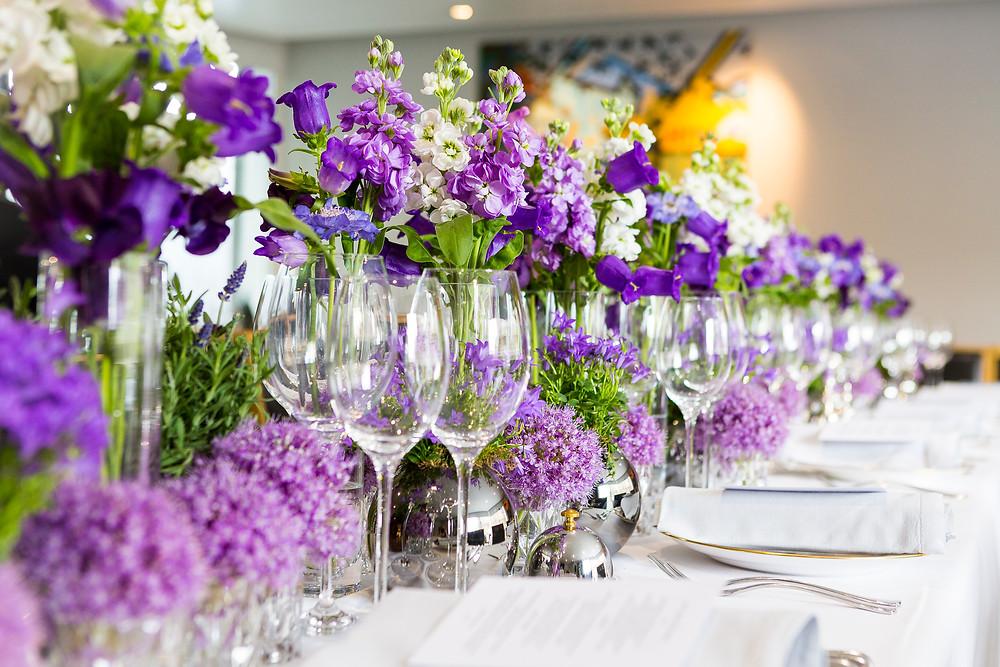 Purple wedding flowers, elegant low table arrangements