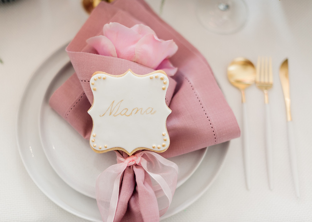 Pink table setting with gold cutlery and personalised cookie