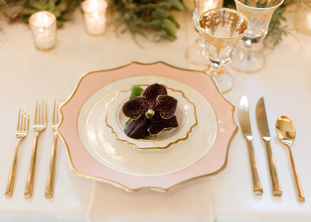 Pink and gold charger plate with gold cutlery and purple orchid