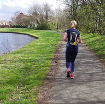 Jogger running along the Forth & Clyde canal path at Dalmuir.  -  23rd March 2019