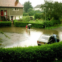 My daughter and her pal having a paddle. Joe, my neighbour decides it would be a good idea to move his car to higher ground. - Whitecrook, Clydebank. 5th July 1985.