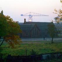 Sun setting behind shipyard crane. The Episcopalian Church on Glasgow Road, photo taken from Dunedin Terrace. - October 1977