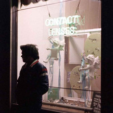 Optician's window next to the Mainbrace pub on Glasgow Road. My nephew, Paul, waiting for a bus. Glasgow Road, Clydebank. 28th March 1978