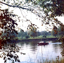 Tranquil scene of a small yacht sailing down the Clyde past the Rothesay Dock. - Photo by Tommy Quinn. October 1978