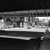 Under the railway bridge looking down Kilbowie Road, the International Bar on the left. Date unknown - Photo by William Duncan