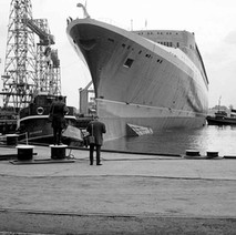 Photographers photographing the QE2 after it has been launched and the tugs are docking the massive hull. - John Brown Shipyard, Clydebank, 1967. Photo by William Duncan