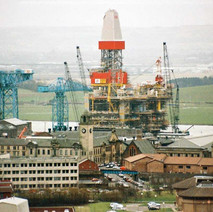 Looking down Clydebank towards the UIE shipyard, A large rig towers over the town. UIE bought the yard in 1980 to build jack-up and semi-submersible rigs.  -  1994