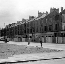 Glasgow Road tenements being demolished. The safety fence is made using doors and floor boards from the tenements themselves. - Photo by William Duncan